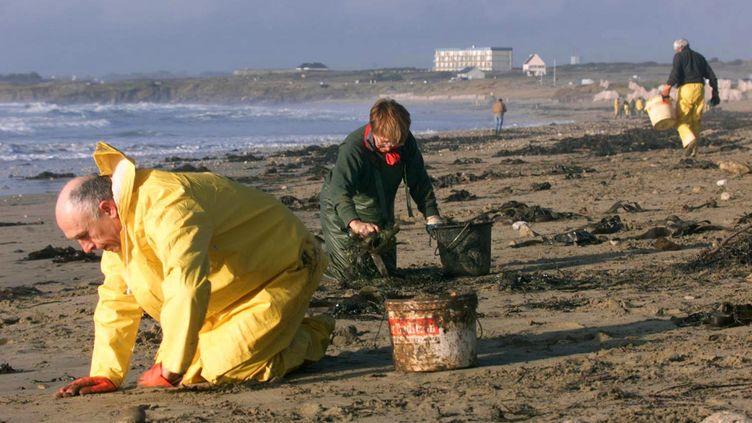 """Des bénévoles ramassent les galettes de fioul rejetées par l'""""Erika"""" sur une plage du Fort-Bloqué (Morbihan), en janvier 2000. (MARCEL MOCHET / AFP)"""