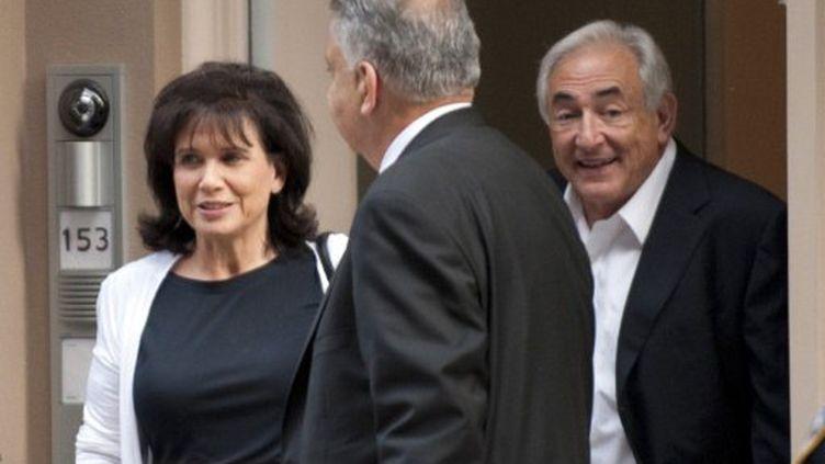 Dominique Strauss-Kahn et son épouse Anne Sinclair, souriants, quittant leur domicile après la séance au tribunal (AFP - DON EMMERT)