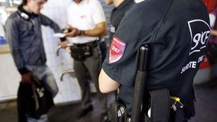 Des policiers en charge de la sécurité du réseau SNCF accompagnent un contrôleur qui verbalise un voyageur, le 5 juillet 2012 à Paris. (THOMAS SAMSON / AFP)