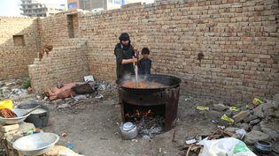 Un Afghan prépare à manger dans un camp de réfugiés à Kaboul, le 12 juillet 2021. (SAYED ZAKERIA / SPUTNIK / AFP)