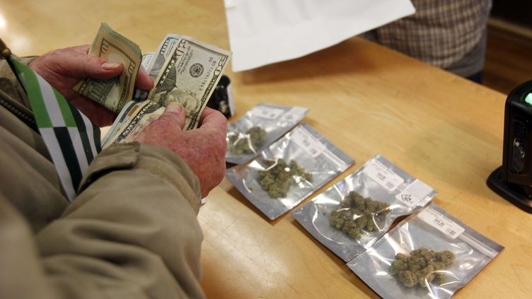 Un client achète du cannabis récréatif dans un dispensaire d'Oakland, en Californie, le 1er janvier 2018. (MATHEW SUMNER / SIPA / AP)