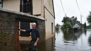 """Un habitant de """"La Gueroulde"""", à côté de Breteuil (Normandie),se tient dans sa rue,inondée. L'Itonest sorti de son lit suite aux pluies le 5 juin 2018. (JEAN-FRANCOIS MONIER / AFP)"""