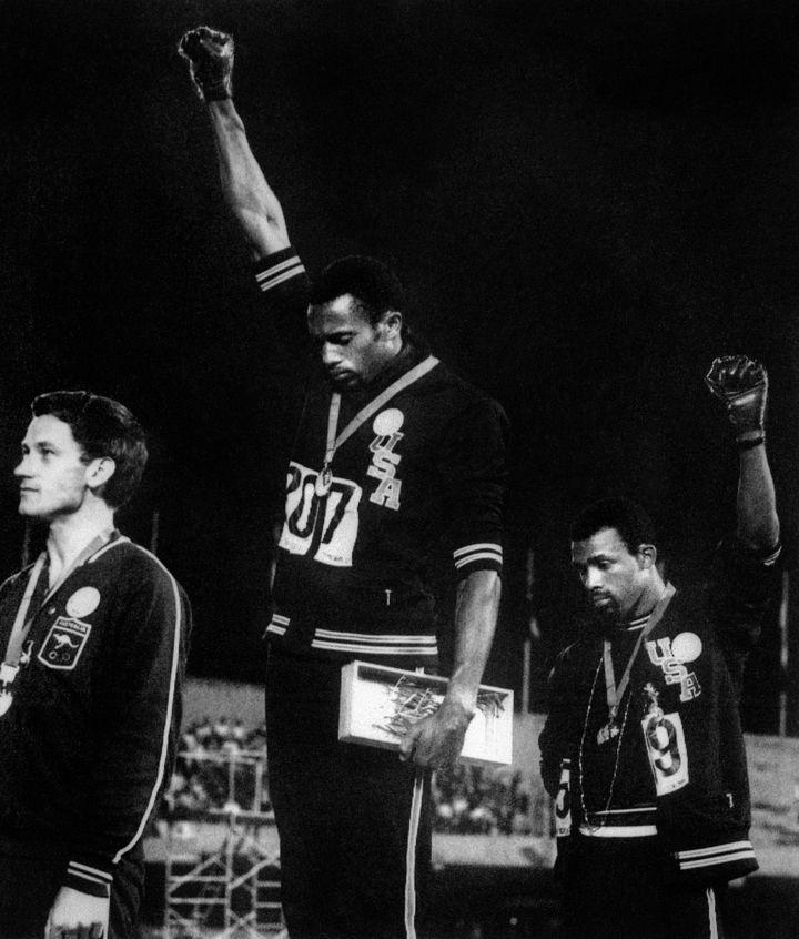 Les athlètes américains Tommie Smith (au centre) et John Carlos (à droite) lèvent un poing ganté en soutien aux mouvements des droits civiques aux Etats-Unis, lors des Jeux olympiques de Mexico, le 17 octobre 1968. (AFP / EPU)