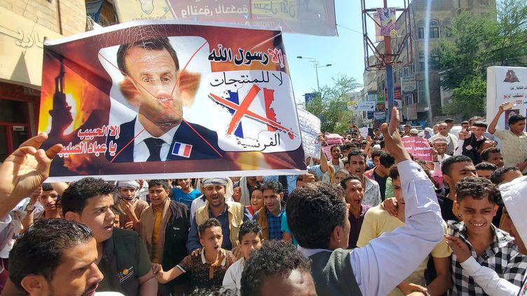 Des manifestants brandissent une affiche avec le visage d'Emmanuel Macron grimé en cochon, aprèsses déclarations défendant le droit à la caricature au nom de la liberté d'expression,le 31 octobre à Taez (Yémen). (AFP)