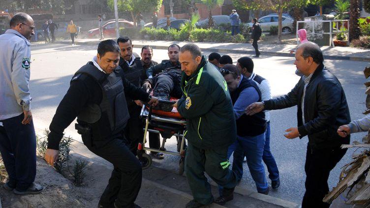 Les secours égyptiens prennent en charge une victime de l'explosion dans les rues du Caire (Egypte), le 9 décembre 2016. (STRINGER / AFP)