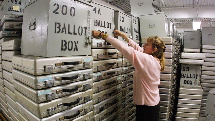 Responsable des votes dans le comté de Palm Beach, en Floride, Theresa Le Pore range des boîtes contenant des bulletins, le 7 novembre 2000, au lendemain l'élection présidentielle controversée, remportée par George W. Bush. (JOE RAEDLE / GETTY IMAGES NORTH AMERICA )