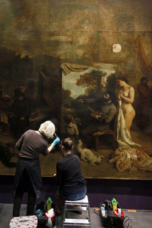 """Deux restauratrices interviennent sur """"L'Atelier du peintre"""" de Gustave Courbet, au musée d'Orsay en décembre 2014  (PATRICK KOVARIK / AFP)"""