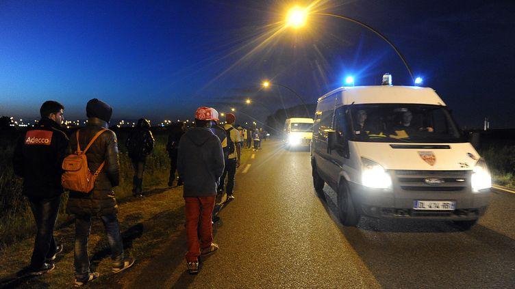 Des migrants passent devant une fourgonnettede CRS, dimanche 2 août 2015 à Calais (Pas-de-Calais). (FRANCOIS LO PRESTI / AFP)