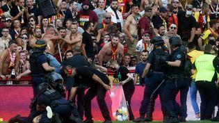 Des policiers anti-émeutes arrêtent un homme après que des supporters de Lens ont envahi le terrain pendant le match de football de L1 français entre le RC Lens (RCL) et Lille (LOSC) au Stade Bollaert-Delelis à Lens, dans le nord de la France, le 18 septembre 2021. (FRANCOIS LO PRESTI / AFP)