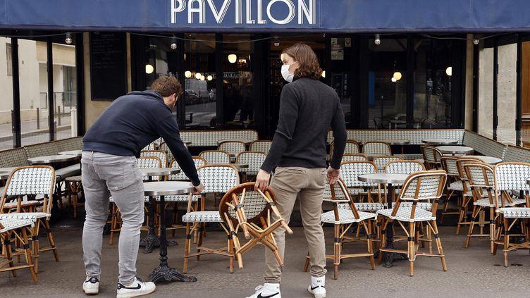 Des employés sont au travail pour aménager la terrasse d'un café, le 17 mai 2021 à Paris. (LUDOVIC MARIN / AFP)