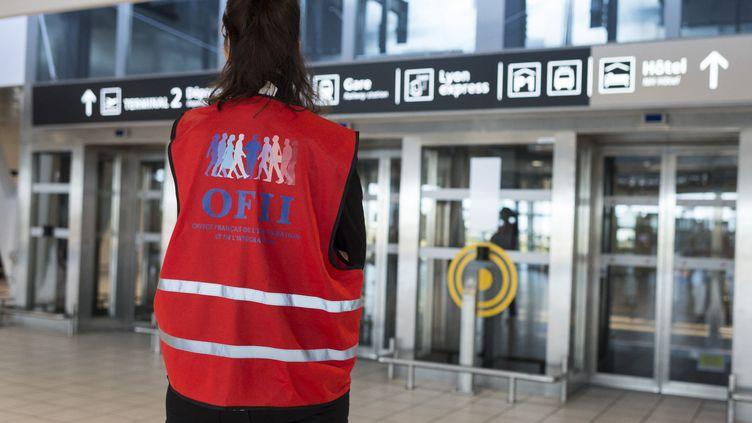 Une bénévole de l'Office francais de l'Immigration et de l'Integration (OFII) attend l'arrivée de migrants à l'aéroport Lyon-Saint-Exupéry en 2017. (ROMAIN LAFABREGUE / AFP)