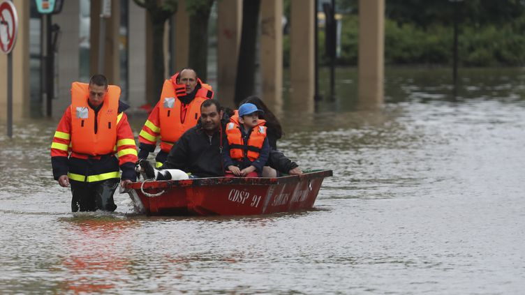 Une famille est évacuée à Longjumeau (Essonne) après les inondations qui ont touché la ville jeudi 2 juin. (KENZO TRIBOUILLARD / AFP)