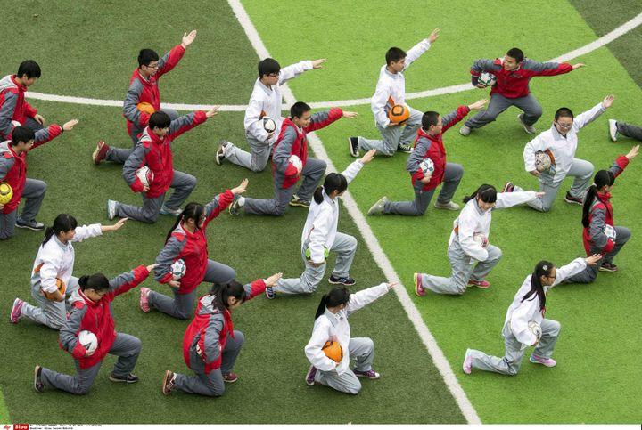 Des élèves participent à un cours de football en mars 2015 dans un collège de Hangzhou, dans la province du Zhejiang, à l'est de la Chine. Le gouvernement chinois a investi dans le développement à long terme du football, en développant notamment les programmes de ce sport dans les écoles du pays.   (AP/SIPA / AP)