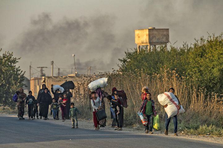 Des civils syriens et kurdes fuient les bombes turquesà Ras al-Aïn, dans le nord-est de la Syrie, le 9 octobre 2019. (DELIL SOULEIMAN / AFP)