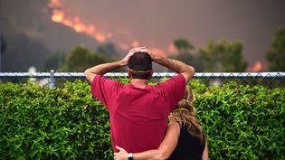 Un couple regarde les flammes se rapprocher de leur maison, le 9 août 2018 à Lake Elsinore (Etats-Unis). (ROBYN BECK / AFP)