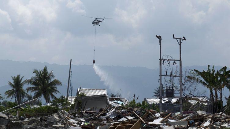 Un hélicoptère asperge un quartier de Palu (Indonésie) avec du liquide désinfectant, le 18 octobre 2018. (YUSUF WAHIL / AFP)