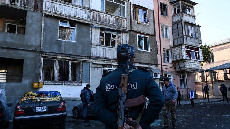 Des policiers devant un immeuble visé par des tirs d'artillerie lourde à Stepanakert, dans le Haut-Karabah, le 3 octobre 2020. (AFP)