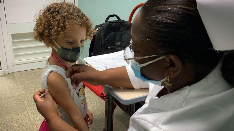 Une infirmière s'apprête à vacciner une fillette, à La Havane (Cuba), le 24 août 2021. (ADALBERTO ROQUE / AFP)