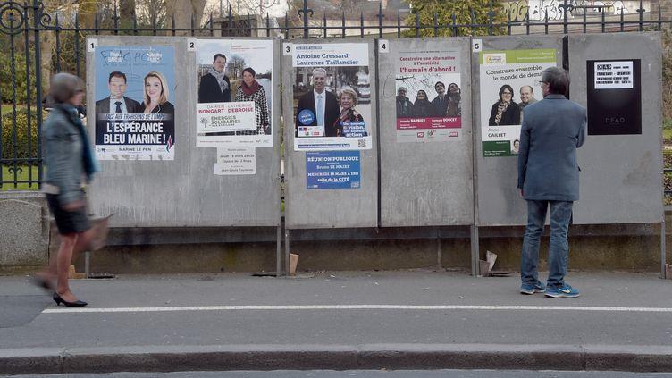 Des passants devant les panneaux électoraux à Rennes (Ille-et-Vilaine), le 17 mars 2015. (DAMIEN MEYER / AFP)