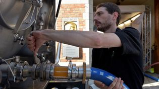 Un employé de la brasserie Halve Mann, à Bruges (Belgique), connecte untuyau de bière à un camion-citerne, le 15 septembre 2016. (ERIC VIDAL / REUTERS)