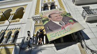 Un manifestant fait tomber un portrait géant du président algérien Abdelaziz Bouteflika à Alger, le 22 février 2019, lors d'une manifestation contre sa candidature à l'élection présidentielle. (RYAD KRAMDI / AFP)