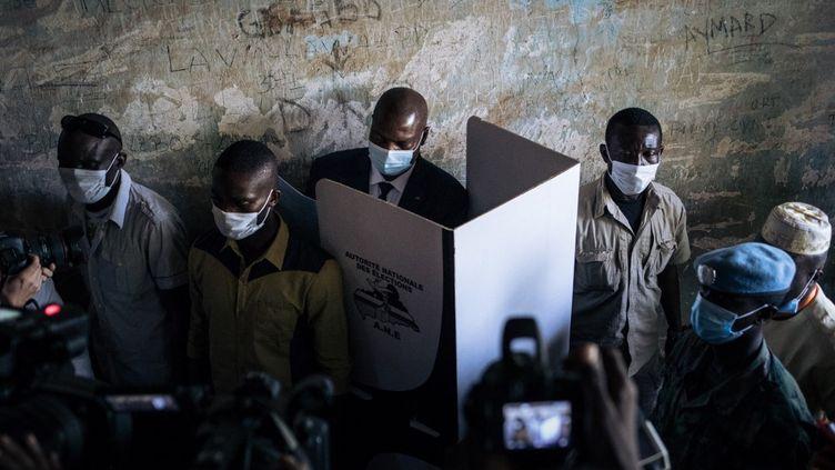 Le président de la République centrafricaineFaustin Archange Touadera vote à Bangui entouré de ses gardes, lors du premier tour des élections législatives le 27 décembre 2020. (ALEXIS HUGUET / AFP)