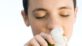Une jeune femme sent une fleur. Photo d'illustration. (MICHÈLE CONSTANTINI / MAXPPP)