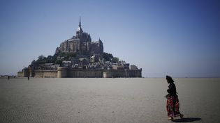 Une femme march au Mont-Saint-Michel (Manche), le 7 mai 2018. (CHARLY TRIBALLEAU / AFP)