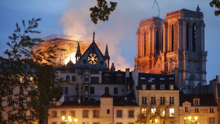 Des pompiers arrosent la toiture de la cathédrale Notre-Dame de Paris pour éviter que l'incendie ne se propage aux beffrois, le 15 avril 2019. (FRANCOIS GUILLOT / AFP)