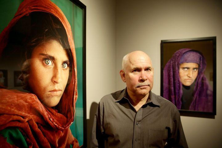 Steve Mc Curry entre deux images de Sharbat Gula. (ULRICH PERREY / DPA / AFP)