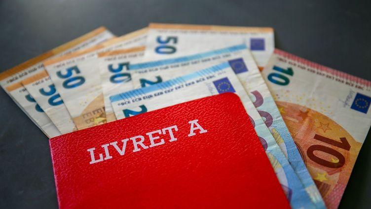 Un livret A avec des billets de banque, le 16 avril 2020 (photo d'illustration). (NICOLAS GUYONNET / HANS LUCAS / AFP)
