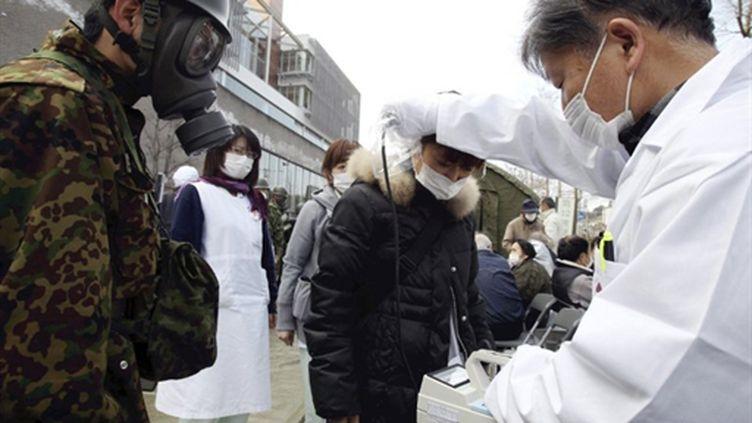 Un médecin utilise un compteur Geiger pour mesurer le taux de radiation d'une femme, près de Fukushima, le 13 mars 2011. (AFP PHOTO / YOMIURI SHIMBNUN)