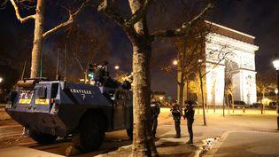 Des policiers dans des véhicules blindés devant l'Arc de triomphe à Paris, le 8 décembre 2018. (MUSTAFA YALCIN / ANADOLU AGENCY / AFP)