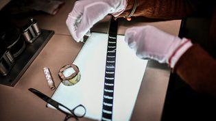 """Laure Marchaut, avec ses outils, qui travaille sur une pellicule du film """"Napoléon"""", d'Abel Gance. (STEPHANE DE SAKUTIN / AFP)"""