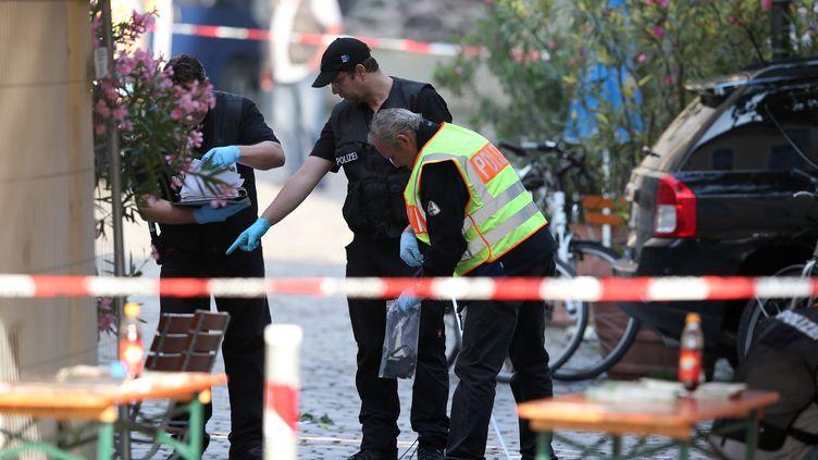 Des policiers sur les lieux de l'attentat suicide perpétré à Ansbach (Allemagne), lundi 25 juillet 2016. (DANIEL KARMANN / DPA / AFP)