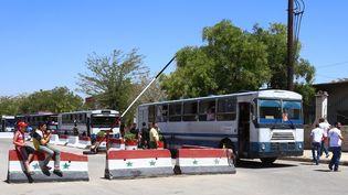 Des bus transportant des familles syriennes passent un check point, à l'entrée de Qadam, dans le sud de Damas (Syrie), le 21 août 2014. (YOUSSEF KARWASHAN / AFP)