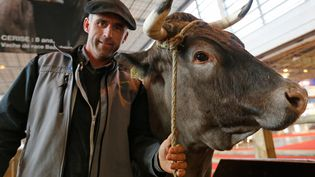 Joël Sillac pose avec sa vache Cerise, choisie pour être la mascotte du Salon international de l'Agriculture, à Paris, le 26 février 2016. (JACKY NAEGELEN / REUTERS)