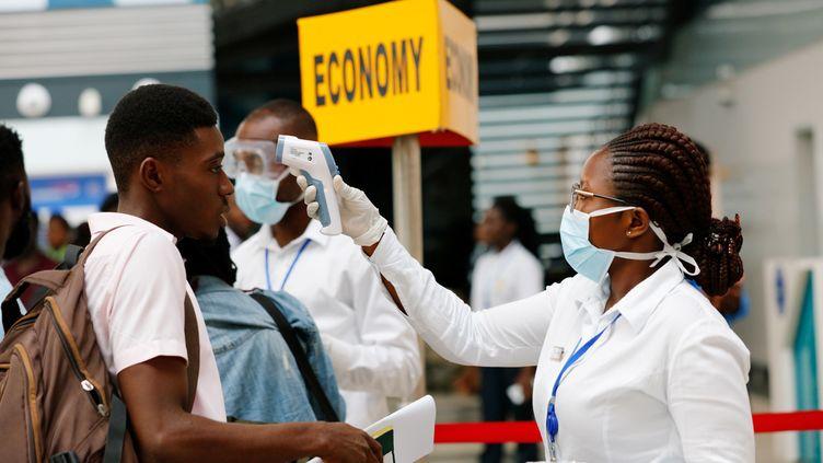 Prise de température d'un passager à l'aéroport international d'Accra. Le Ghana fait partie des pays africains qui ont fermé leurs frontières aux étrangers venant des pays les plus touchés. (FRANCIS KOKOROKO / X03672)