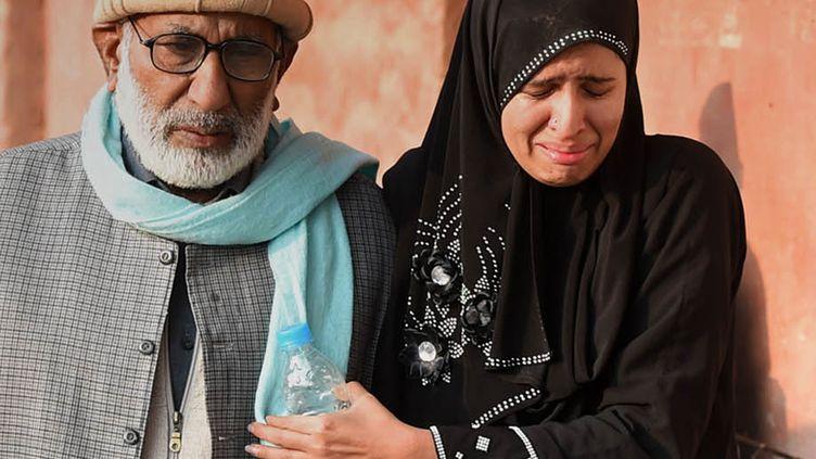 Une femme et un homme arrivent à proximité de l'école de Peshawar (Pakistan) où a eu lieu une attaque terroriste faisant 141 morts dont 132 enfants, le 16 décembre 2014. (A MAJEED / AFP)