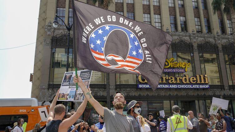 Un manifestant brandit un drapeau à la gloiredu mouvementQAnon, le 22 août 2020, à Los Angeles (Etats-Unis). (KYLE GRILLOT / AFP)