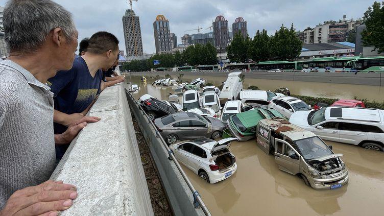 Des personnes regardent des voitures englouties par les eaux après les fortes pluies qui ont frappé la ville de Zhengzhou, dans la province centrale du Henan, en Chine, le 21 juillet 2021. (STR / AFP)
