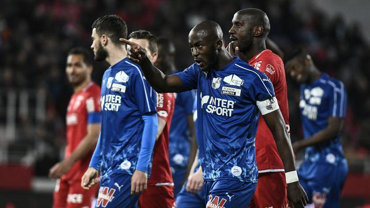 Le joueur d'Amiens Prince Gouano pointe du doigt les tribunes après avoir entendu des cris racistes, le 12 avril 2019 à Dijon (Côte d'Or). (JEFF PACHOUD / AFP)