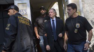 Le président du comité olympique brésilien, Carlos Nuzman, escorté par la police fédérale, à Rio de Janeiro, le 5 octobre 2017. (MAURO PIMENTEL / AFP)