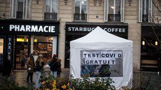 Des personnes font la queue devant une tented'une pharmacie installée pour faire un testantigénique de dépistage duCovid-19, le 21 décembre 2020 à Paris. Photo d'illustration. (MARTIN BUREAU / AFP)