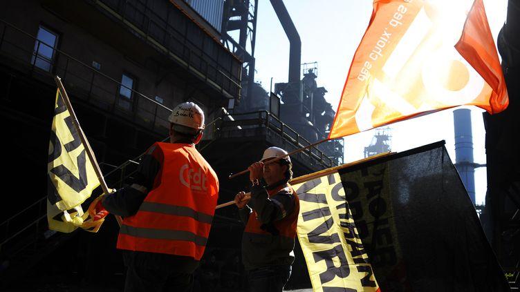 Des représentants syndicaux de la CFDT installent un drapeau noir sur le site ArcelorMittal de Florange (Lorraine), le 25 avril 2013, peu après la fermeture définitive des hauts-fourneaux. (JEAN-CHRISTOPHE VERHAEGEN / AFP)