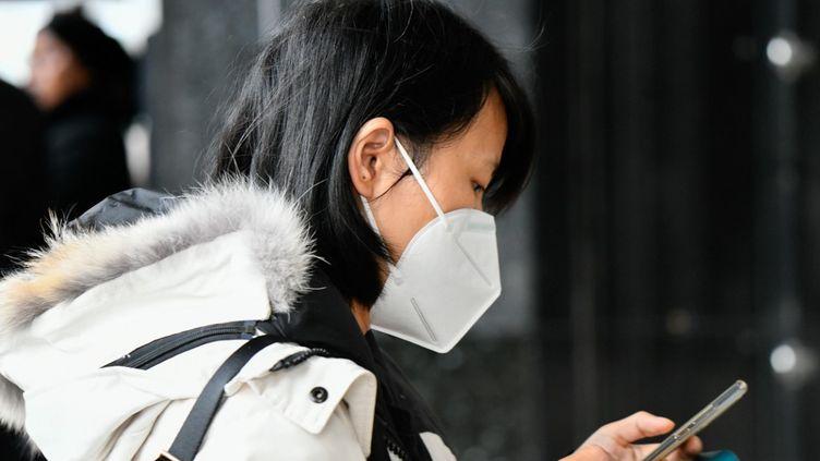 Une femme porte un masque chirurgical à Paris, le 3 mars 2020. (JULIEN MATTIA / ANADOLU AGENCY / AFP)