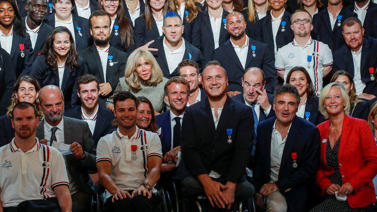 Le président de la république Emmanuel Macron, et son épouse Brigitte, posent avec les médaillés français des Jeux olympiques et paralympiques de Tokyo, reçus à l'Elysée le 13 septembre 2021. (BENOIT TESSIER / AFP)