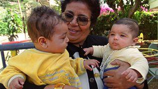 Aicha Ech-Channa, tenant deux bébés dans le jardin de son association pour mères en difficulté, à Casablanca, en mai 2000. (ABDELHAK SENNA / AFP)
