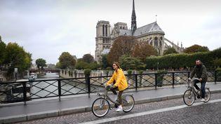 Des cyclistes devant la Cathédrale Notre-Dame lors de la journée sans voiture à Paris, le 1er octobre 2017. (ERIC FEFERBERG / AFP)