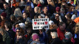 """Une participante du défilé organisé samedi 24 mars 2018 à Washington pour réclamer plus de contrôle des armes à feu brandit une pancarte où il est inscrit """"Protégez les enfants, pas les armes"""". (MANDEL NGAN / AFP)"""